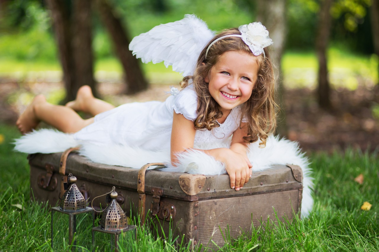 Small-cute-angel-resting-on-the-suitcase