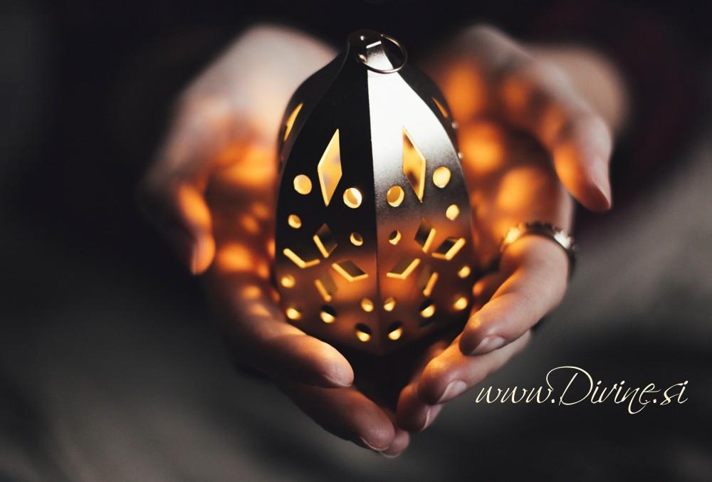 Hands of a woman holding a golden lantern.